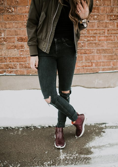 girl standing in black jeans with bomber jacket and nike boots