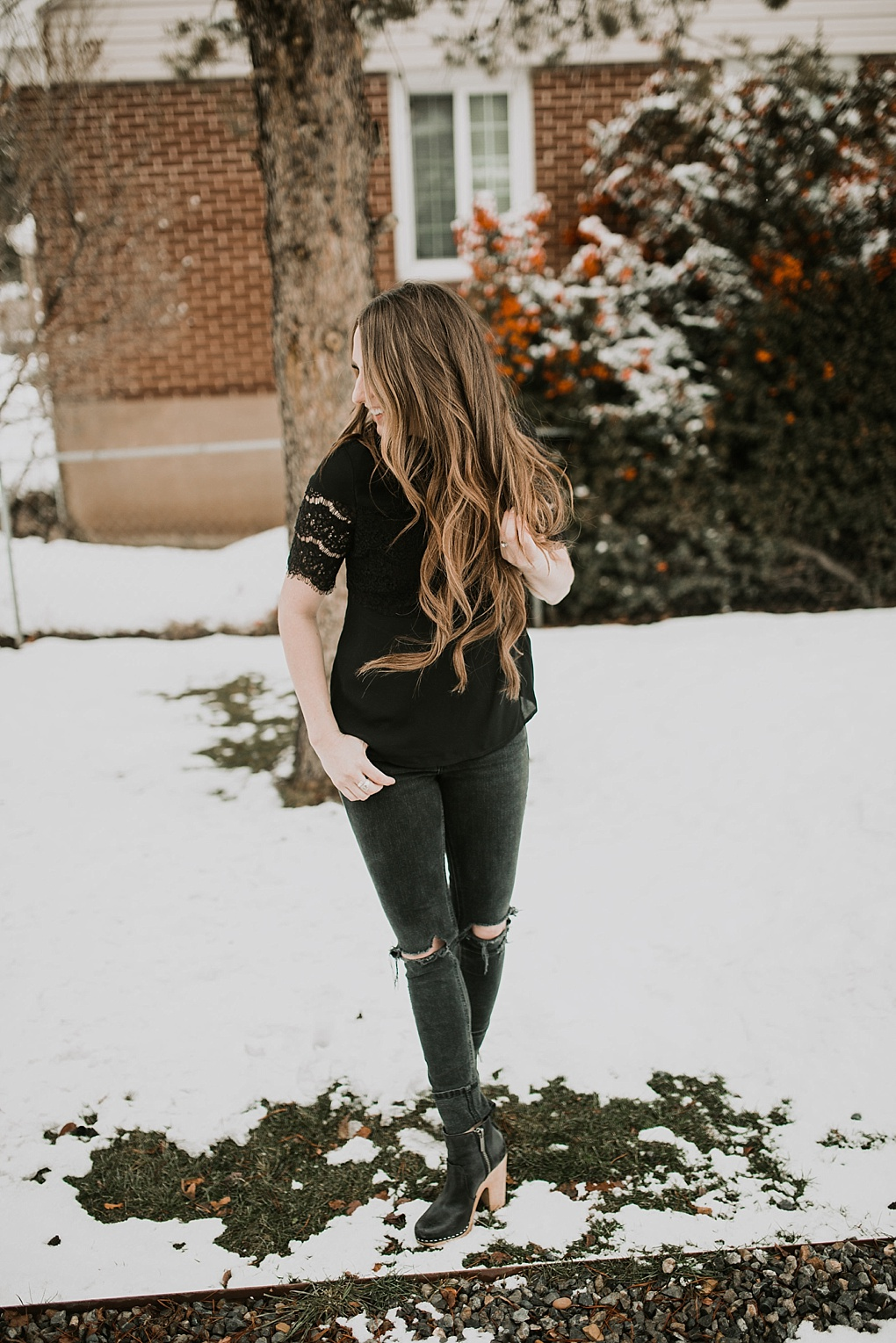 girl standing in snow in black lace top with black jeans and nike boots
