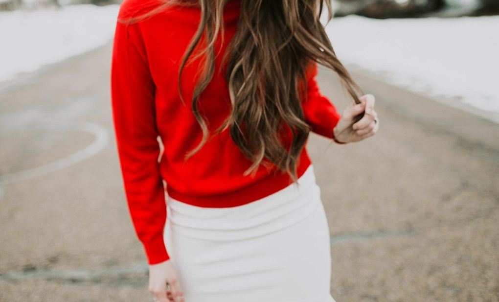 red mockneck turtleneck with jeans and sneakers girl standing in snow with long loosely curled brown hair with caramel highlights