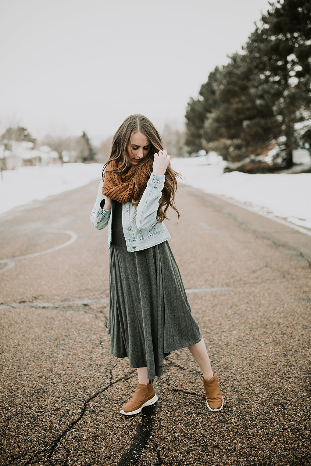 girl standing in road in oversized grey dress with denim jacket brown knit infinity scarf nike boots