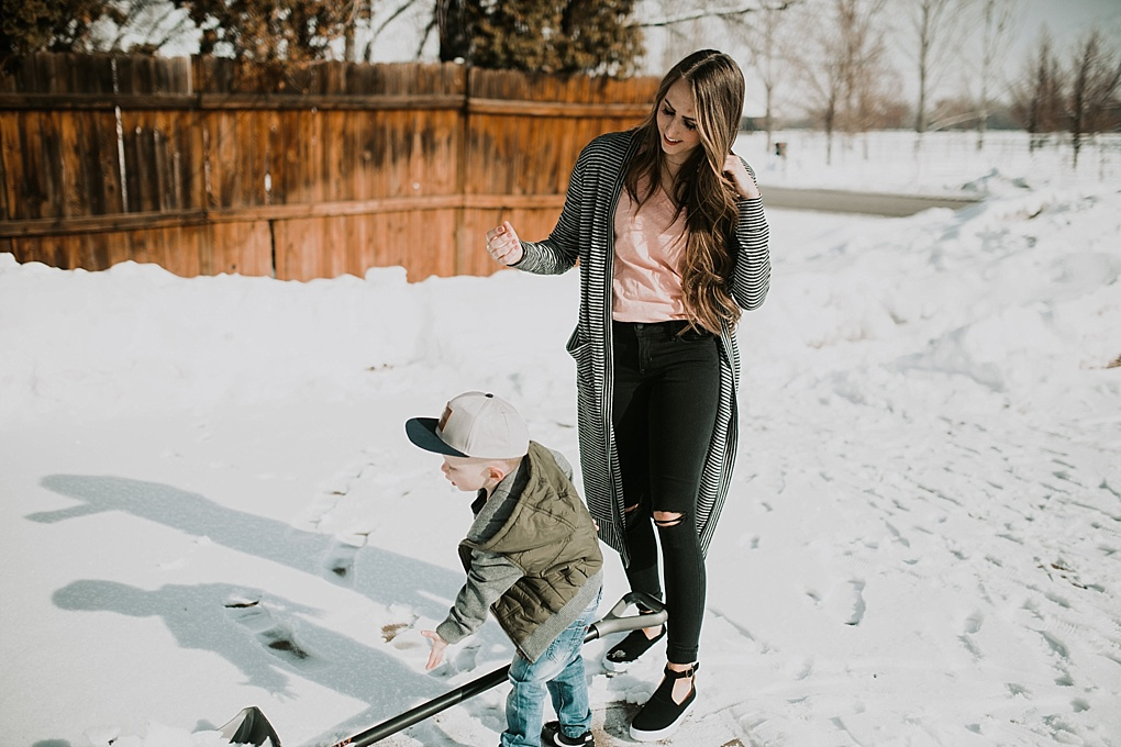 mom and little boy outside shoveling mom in long black and white stripe cardigan and little boy in army puffy jacket with jack and winn hat
