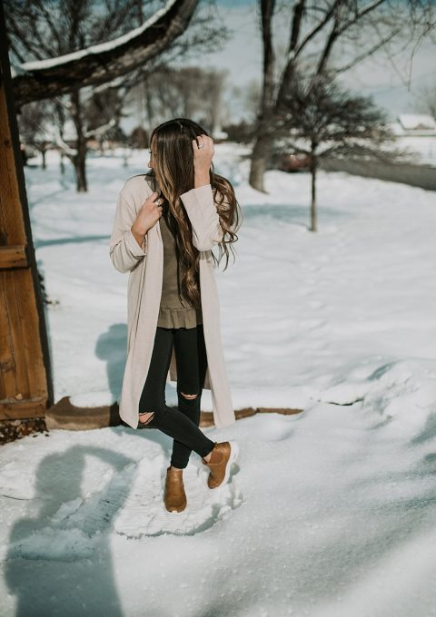 cream duster cardigan with olive peplum top black jeans and nike boots with long loose brown hair with caramel highlights curled