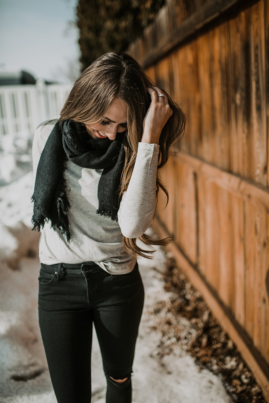 3 ways to tie blanket scarves girl standing in snow in basic tee black jeans and wearing a black blanket scarf
