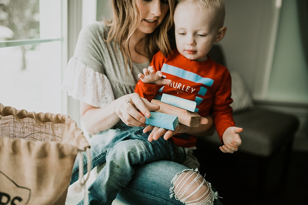 mom and little boy sitting in window seat playing with scraps wood blocks mom in grey top with crochet sleeves and little boy in hurley red tee shirt