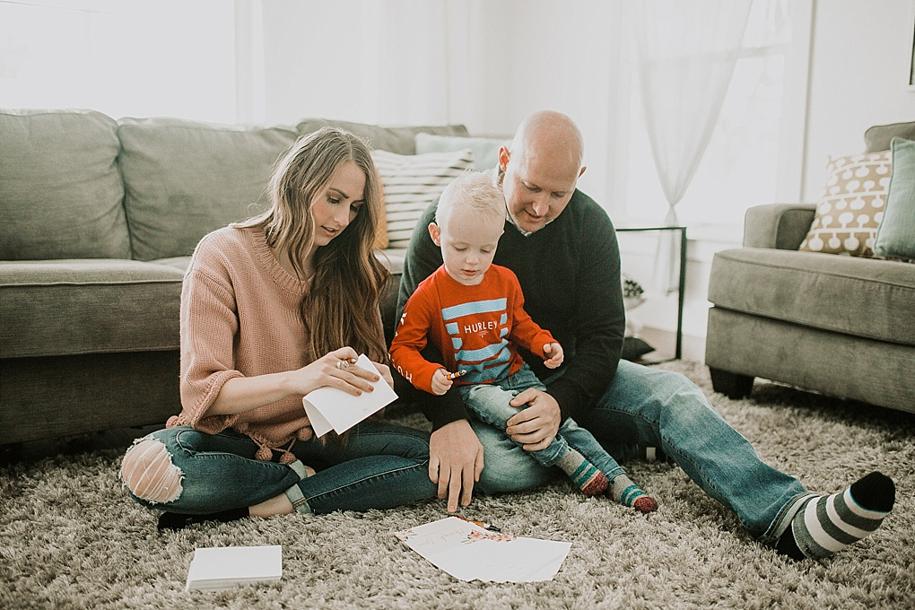 mom dad and little boy writing thank you cards from basic invite on rug in family room mom wearing pom pom sweater