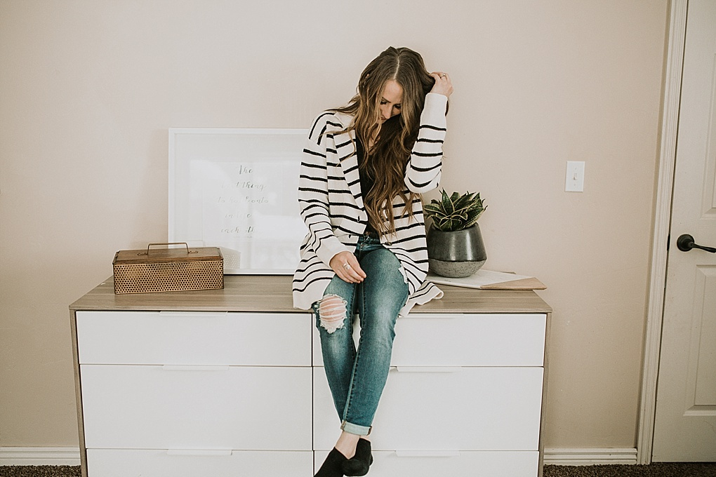 Wonderland by Alice Lane home decor that is affordable and beautiful I love the metal and wood box with the black and concrete planter and the marble and wood slab girl sitting on dresser in cara loren cardigan and jeans