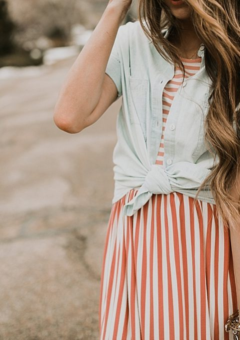 girl standing in road in pink stripe dress downeast basics with denim button up shirt over top with long loosely curled brown hair