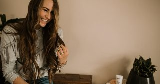 girl sitting on dresser in ruffled sweatshirt with dove deodorant with long loosely curled brown hair