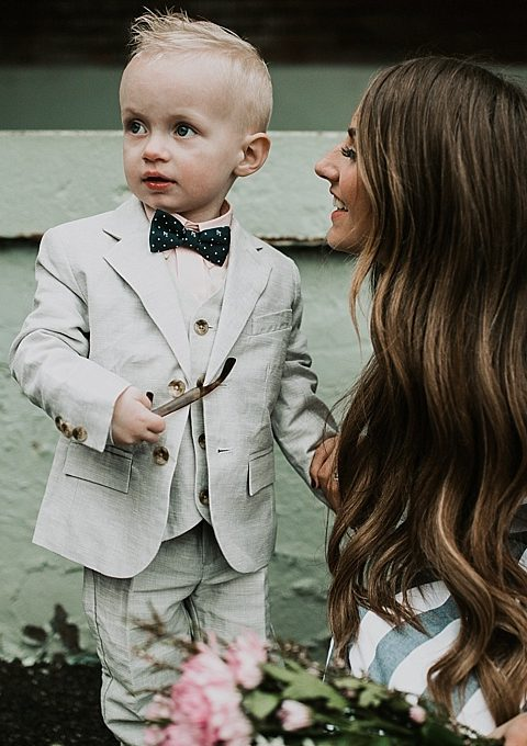 mom and little boy walking little boy in janie and jack linen suit and mom in blue and white stripe shabby apple dress