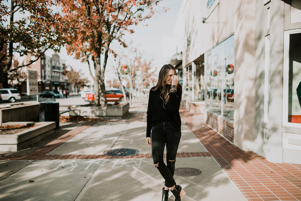 monochromatic black on black look with chunky black turtle neck black jeans and black booties
