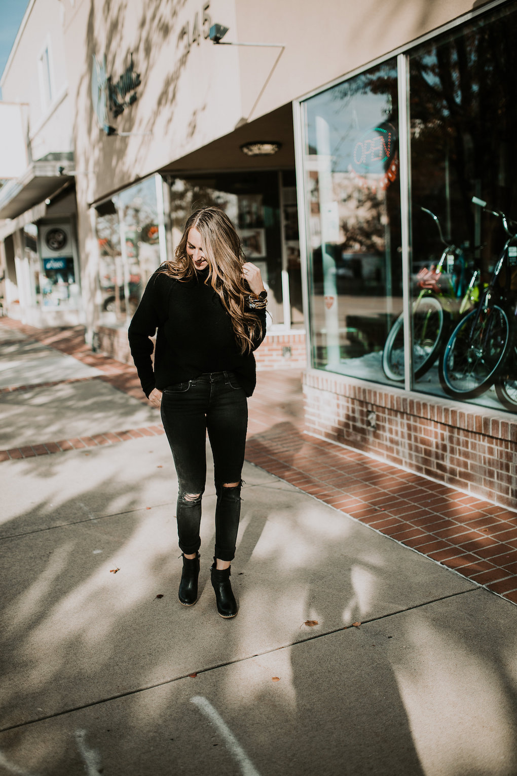girl standing wearing black sweater and black jeans in the middle of the sidewalk