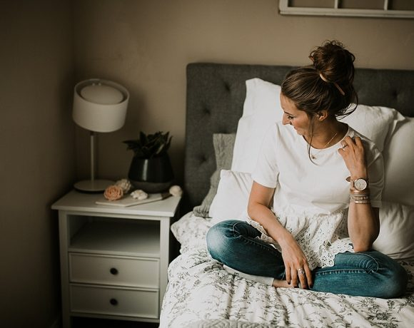 girl sitting on bed in white lace top jeans and top knot with sola wood flowers