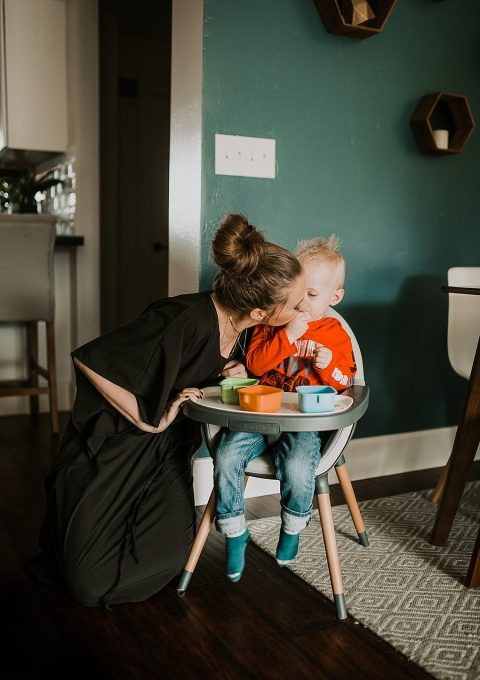 mom and little boy sitting in skip hop high chair mom in lucky love house dress giggling
