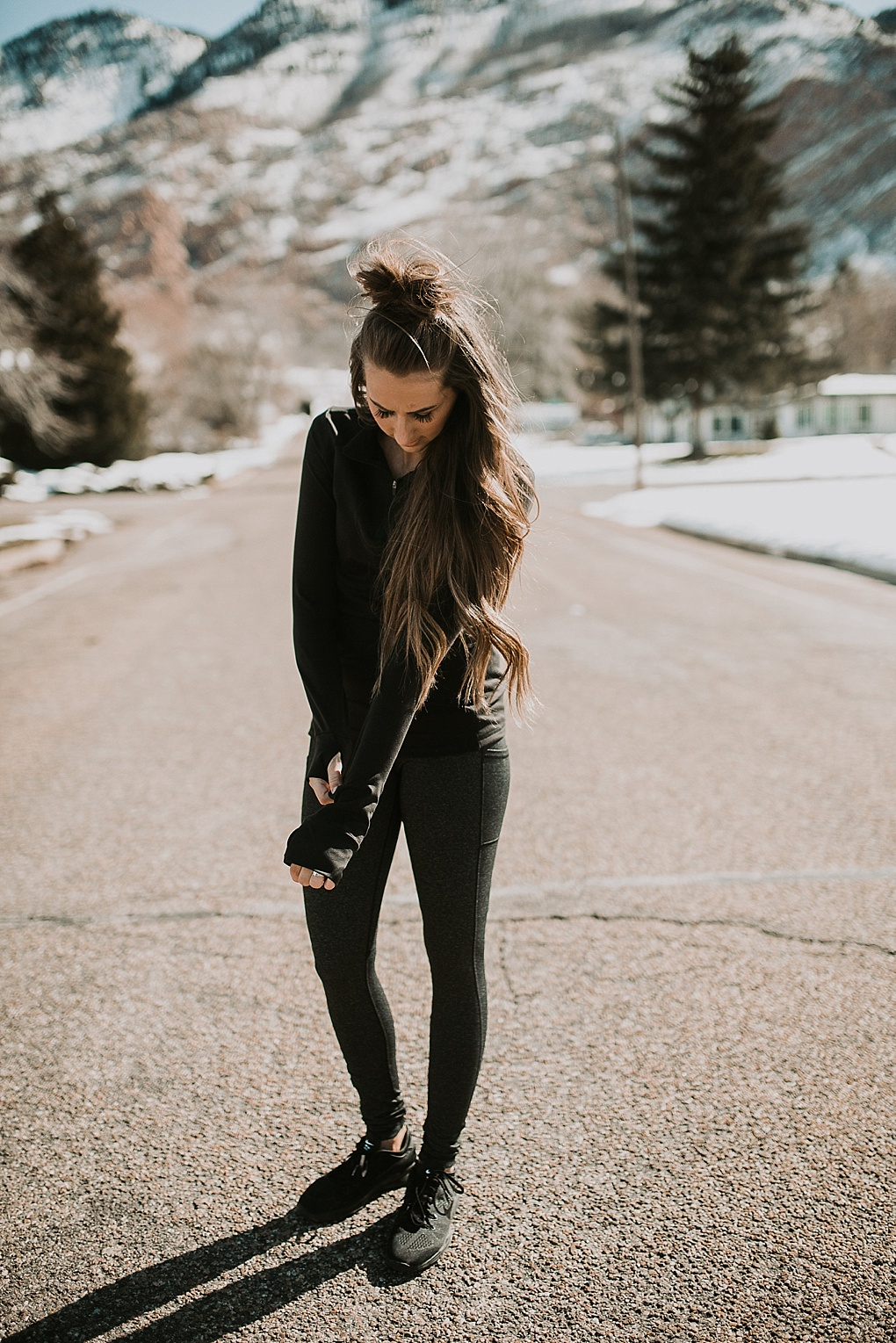 girl standing in road in senita athletics half zip jacket and yoga pants with half up top knot