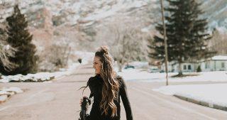 girl standing in road in senita athletics half zip jacket and yoga pants with half up top knot