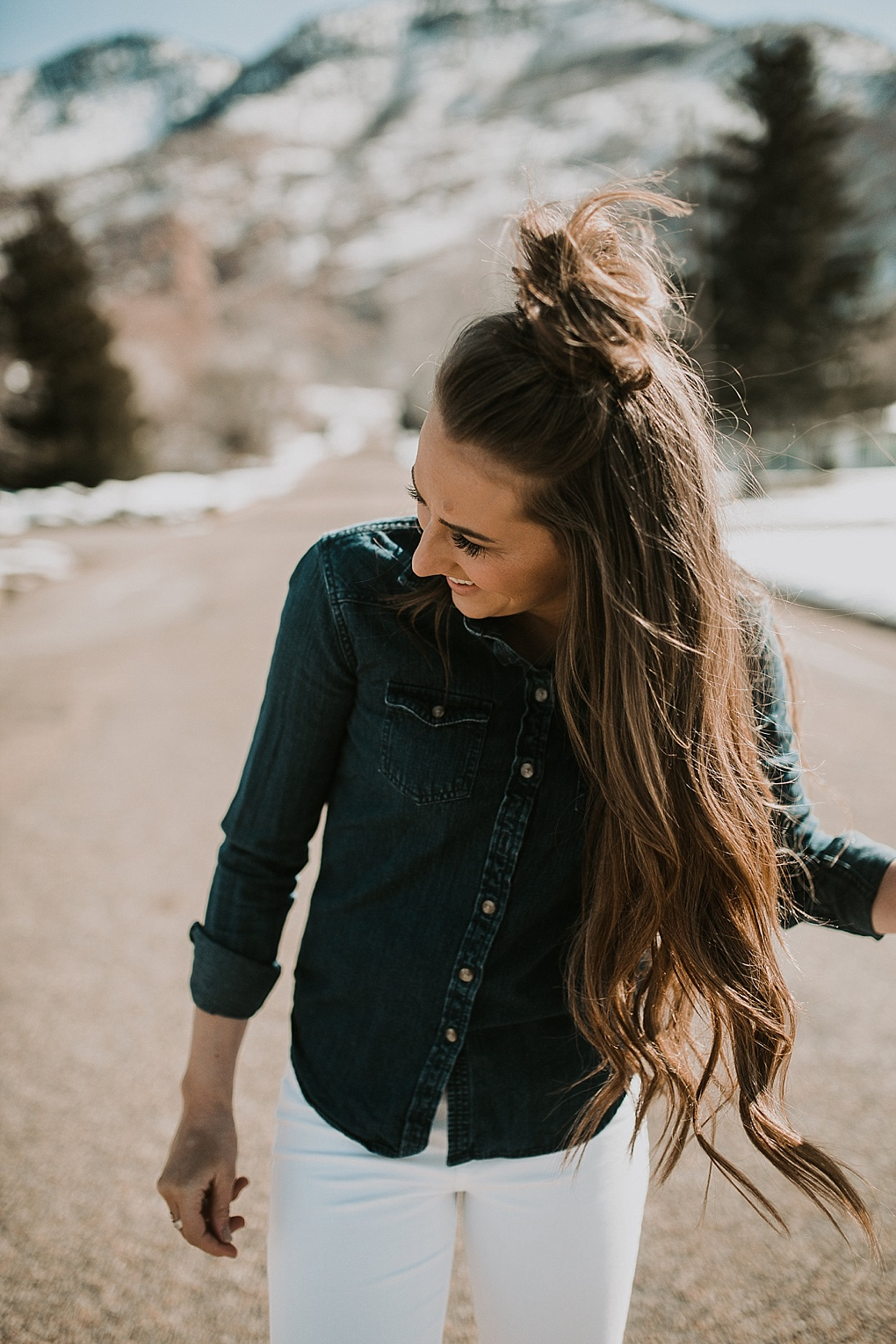 girl standing in the road in white jeans with a denim button shirt with loosely curled brown hair with half up top knot