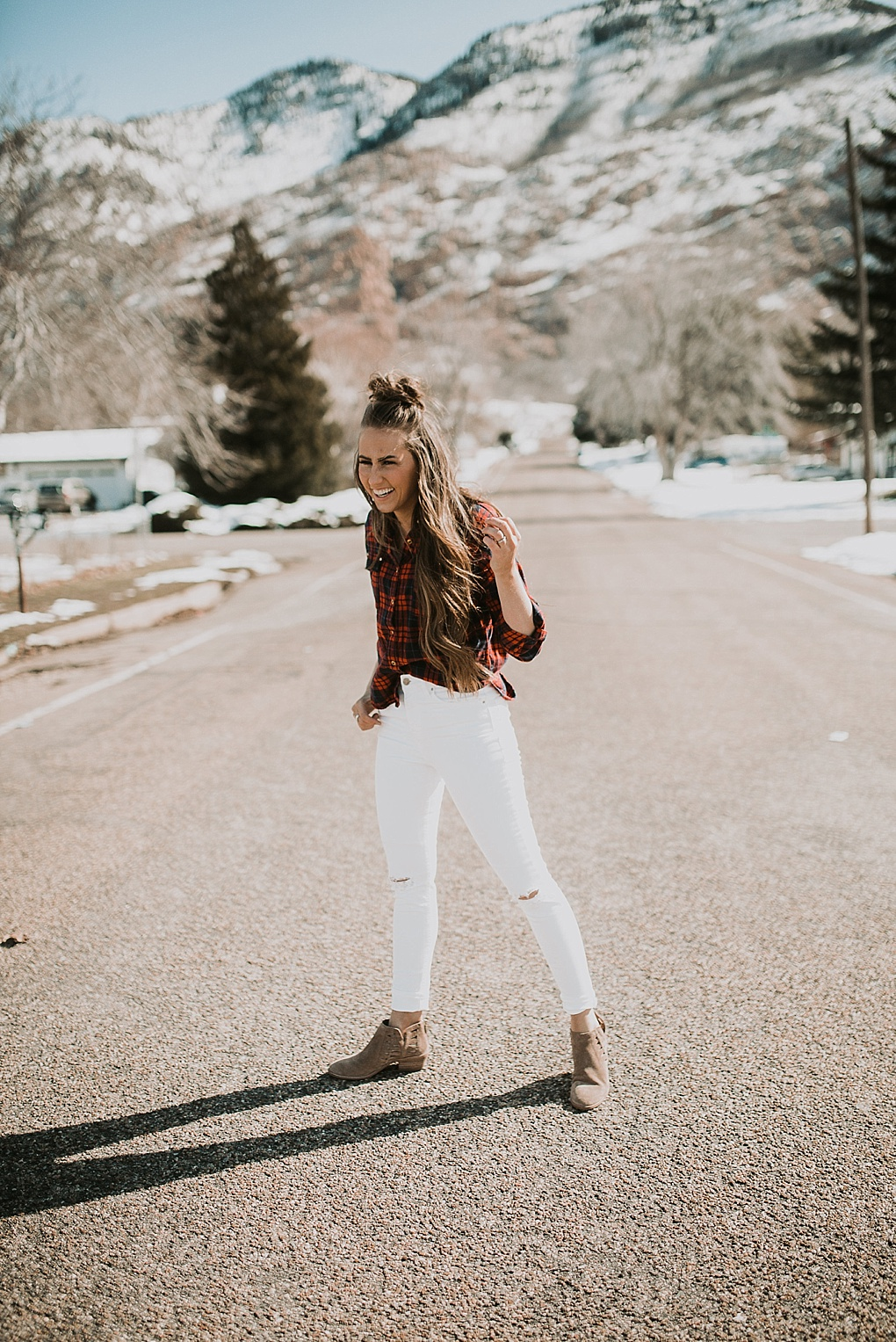 girl standing in road wearing flannel shirt with white jeans and hair loosely curled with half up top knot