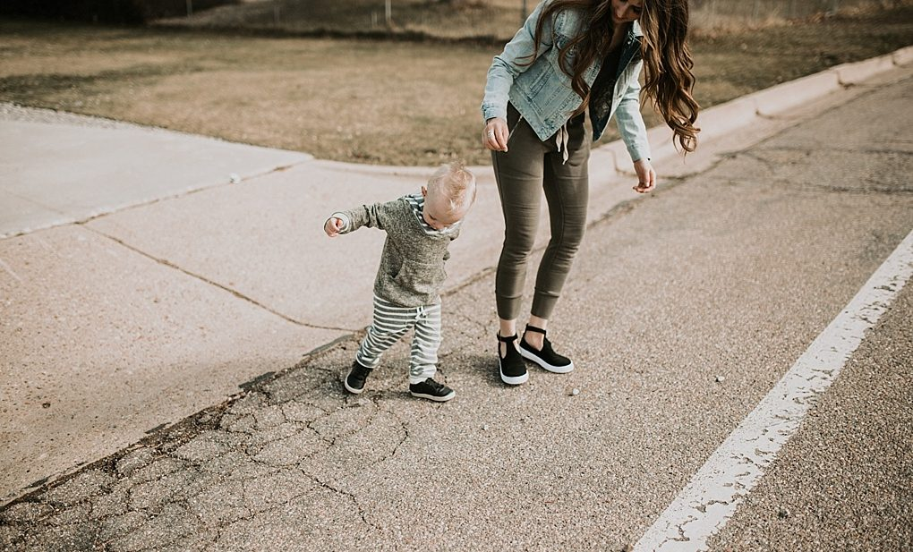 mom in jogger sweats with denim jacket and little boy in lulu and roo sweat outfit walking in the street little boy in freshly picked moccs