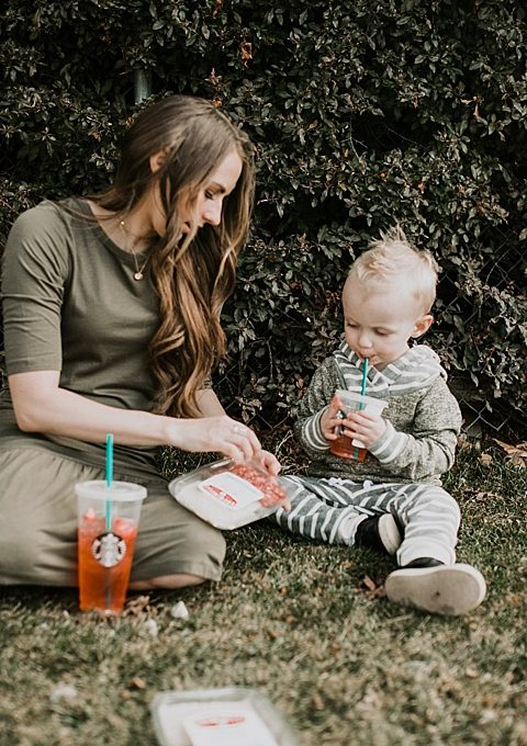 Mom and Little Boy sitting outside snacking with creminelli meats from starbucks