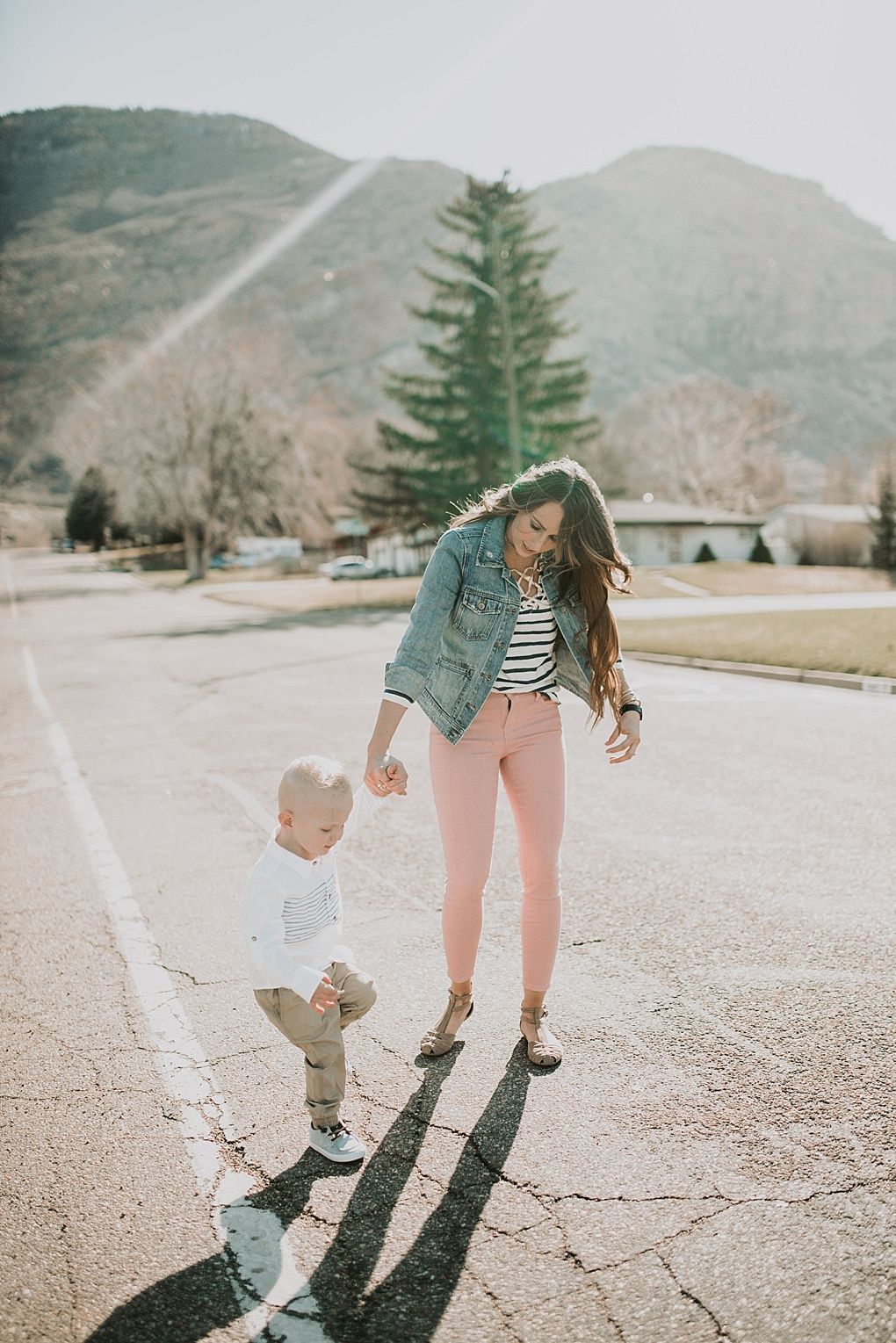 mom in blush pants with nautical stripe old navy top and jean jacket walking in the road with little boy in khaki joggers and white button up with blue stripes