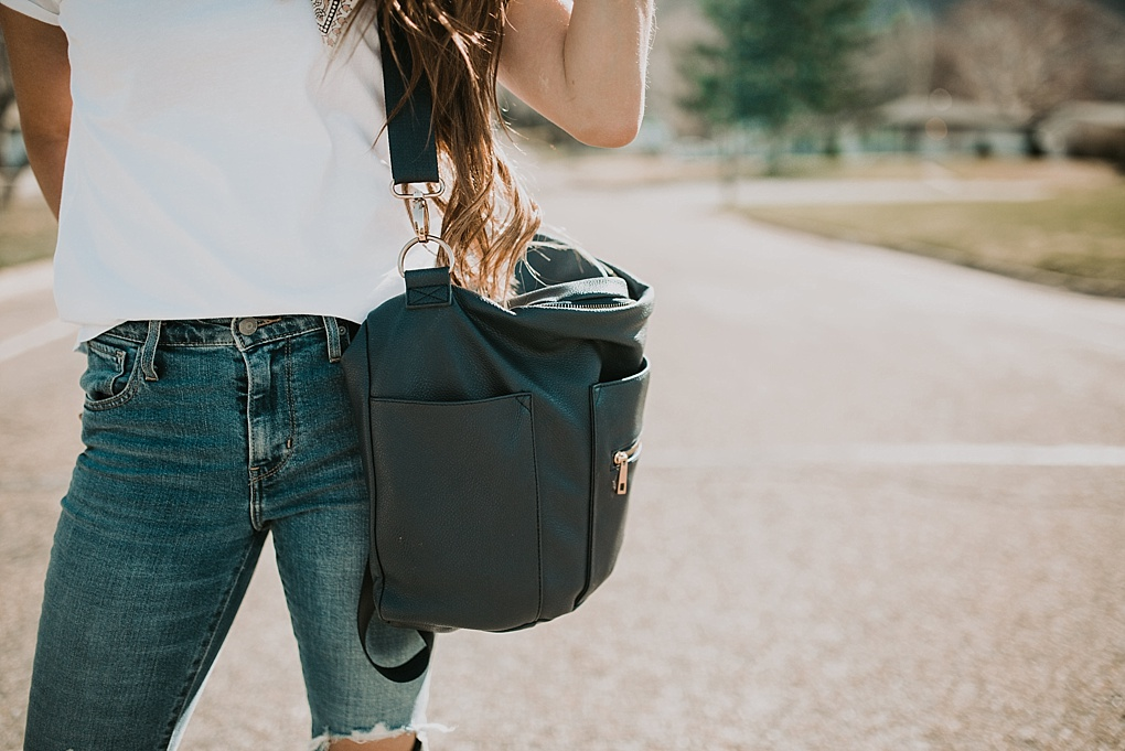 girl standing in road in white embroidered tee shirt with neck scarf and high waisted distressed denim jeans and fawn design diaper bag with long brown hair with caramel highlights loosely curled