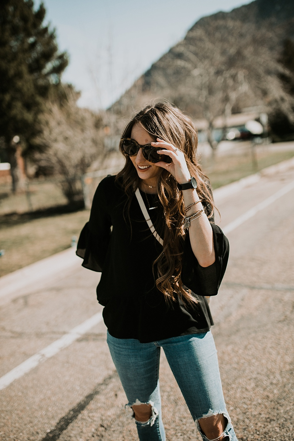girl standing in road with karen walker sunglasses on with levi distressed high waisted jeans michael kors crossbody bag and flats on with loosely curled brown hair with caramel highlights