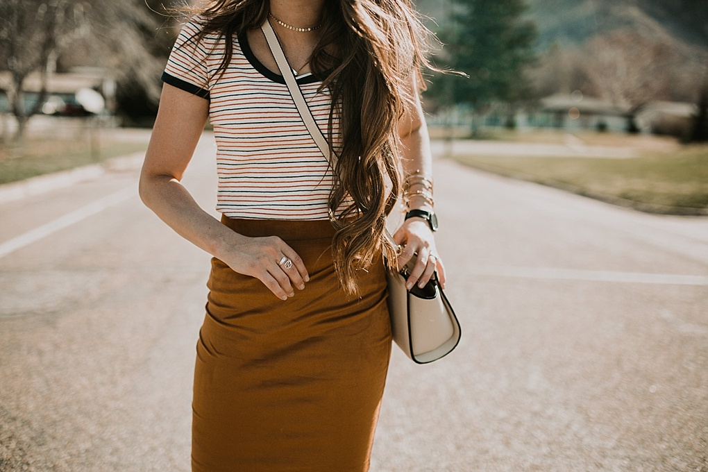 girl standing in street in navy and red stripe madewell tee shirt with gold suede pencil skirt and sneakers on with long loosely curled brown hair with caramel highlights michael kors crossbody bag and karen walker sunglasses