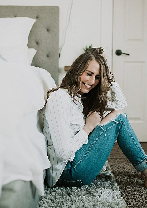 girl sitting on bed in white topshop tie top with distressed jeans and long loose curls and caramel highlights with brittany spears fragrence