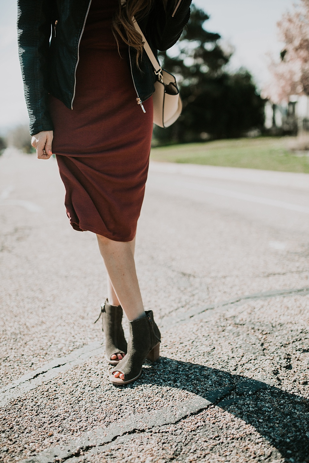 girl standing in road in maroon t shirt dress with toms wedges and long loosely curled brown hair with caramel highlights with leather jacket on and michael kors crossbody bag