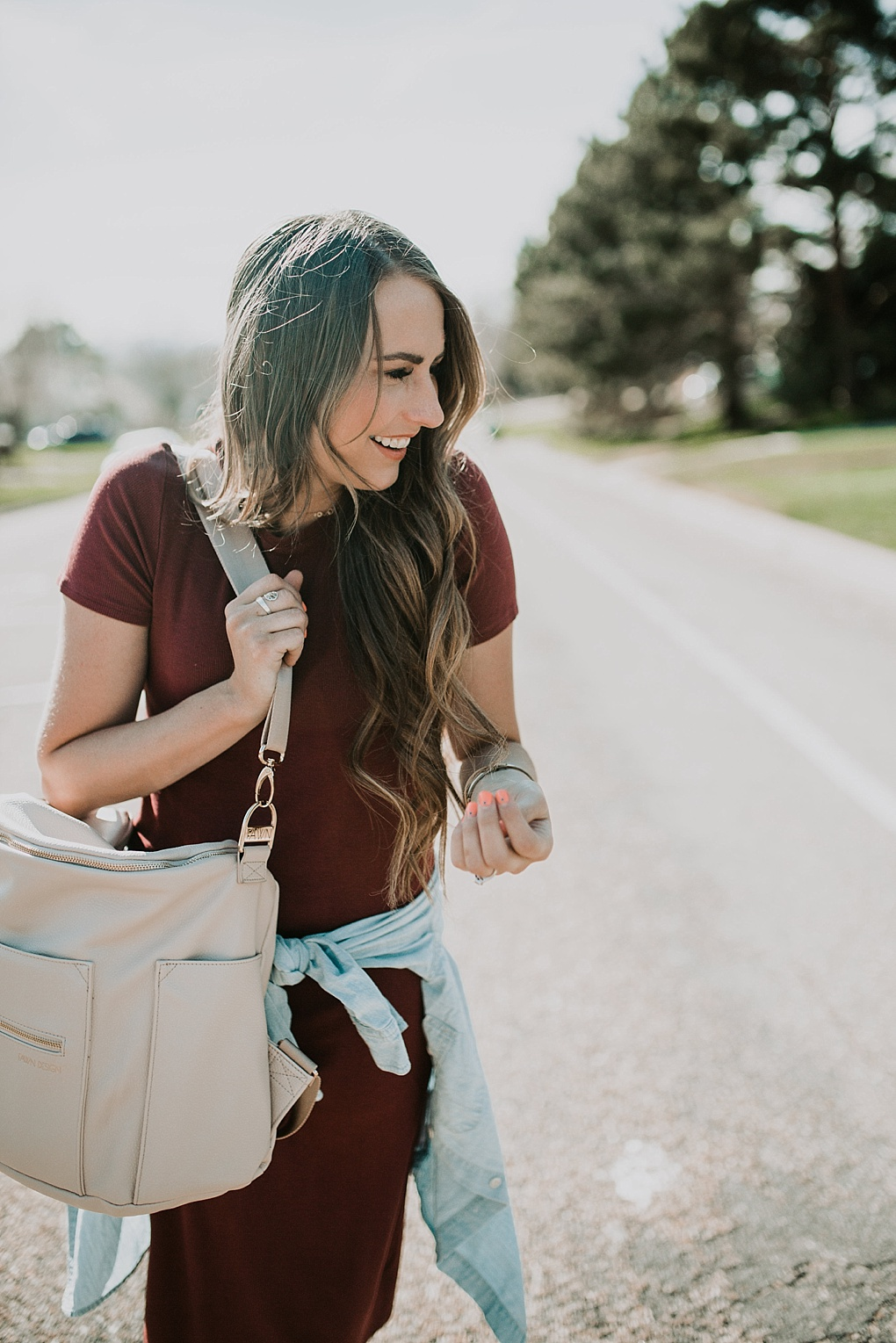 girl standing in road in maroon t shirt dress with target sandals and long loosely curled brown hair with caramel highlights with denim shirt tied around waist and fawn design bag