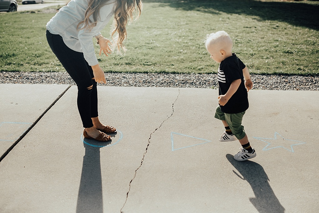 little boy playing outside games with his family football catch blowing bubbles jumping on shapes in june and january wiht mom in denim button down and black jeans with long loosely curled brown hair with caramel highlights