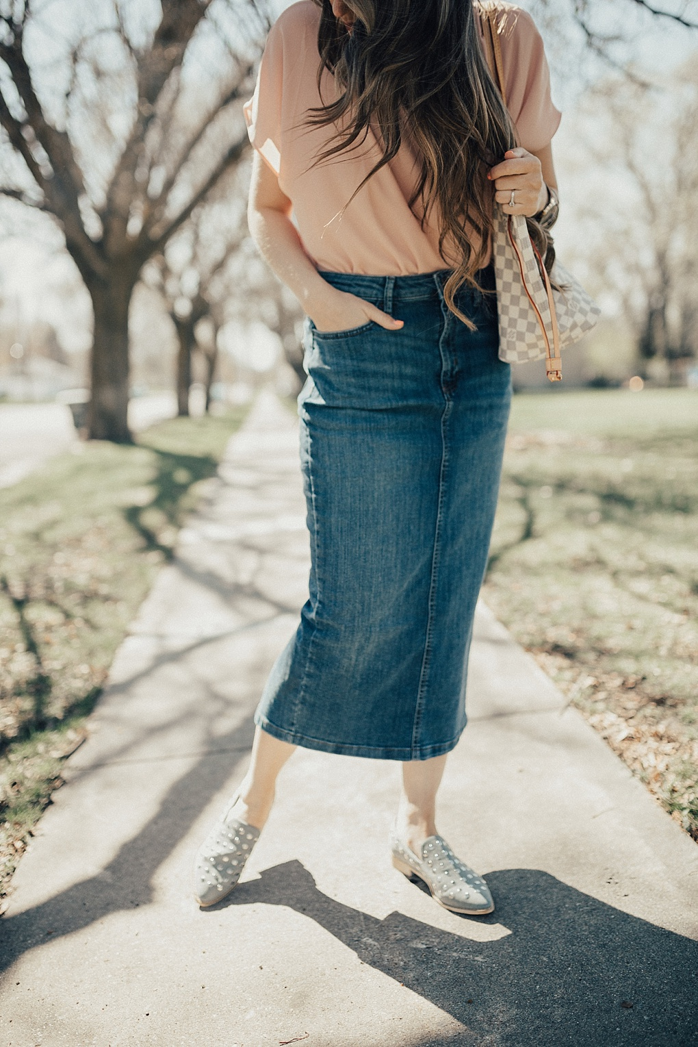 how to dress up and dress down a chiffon top with a denim skirt and jeans with long loosely curled brown hair and studded booties on
