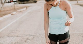 turquoise tank top with mesh black leggings with girl in top knot and nike sneakers
