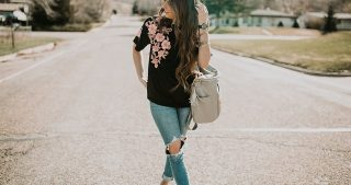 high waist jeans with black floral embroidery fawn design bag long loosely curled brown hair and blush suede sneakers