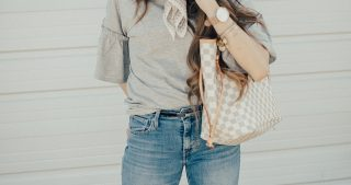 ruffle sleeve top with denim jeans and velvet sneakers with luis vitton bag and loosely curled brown hair