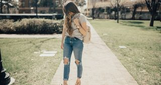 embroidered top with high waisted denim distressed jeans with wedges and fawn design backpack with long loosely curled brown hair