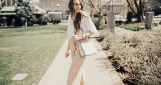 girl standing on sidewalk wearing culottes in blush pink with ruffle sleeved white tee michael kors crossbody bag and long loosely curled brown hair with caramel highlights