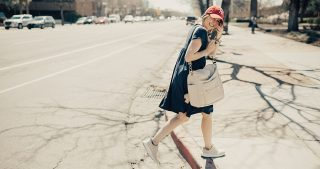 girl crossing street in blue dress with red baseball hat and nike sneakers with fawn design bag