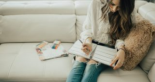 girl sitting and writing in erin condren planner and notebook with organization tips