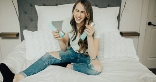 girl sitting on bed using tula products cleanser moisturizer and ph gel