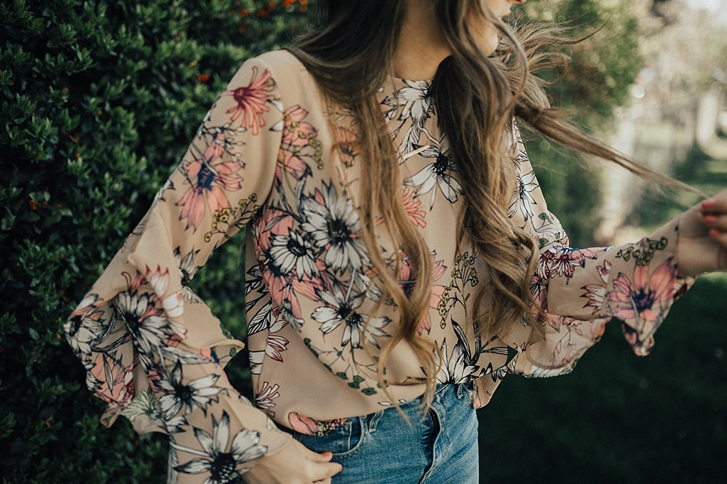 girl standing outside by greenery in floral ruffle top chicwish with long loosely curled brown hair with caramel highlights and high waisted levi jeans