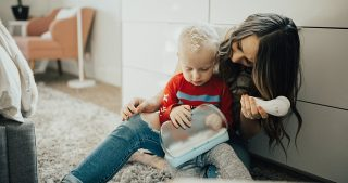 mom and little boy sitting on floor against white IKEA dresser with Vanity Planet Spin Brush laughing and giggling long brown hair with caramel highlights toddler joggers