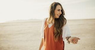 girl standing at salt flats in orange jumper with ruffle sleeved tee shirt under it with long loosely curled brown hair with caramel highlights