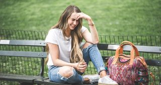 girl standing in NYC Central Park in Nordstrom ripped neckline white t shirt and high waisted levi jeans with marc fischer wedges and nena and co weeknder long loosely curled brown hair