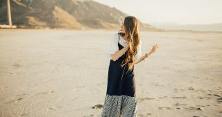 girl standing at salt flats in gingham jumper with white ruffle tee shirt with long loosely curled brown hair
