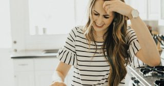 girl standing in the kitchen with forte elements amino acid drink in stripe ruffle sleeve top and long loosely curled brown hair with caramel highlights