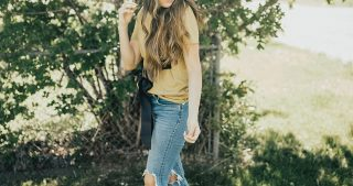girl standing in mustard tie top with black ribbon with high waisted levi jeans and raybans sunglasses