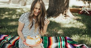 dixie summer plates and fruit angel food cake girl sitting at picnic on the grass on bright colored blanket