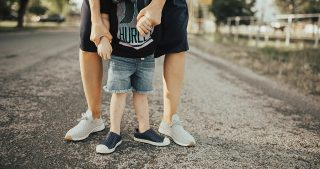 mom and little boy standing in the street wearing Native shoes and a navy dress