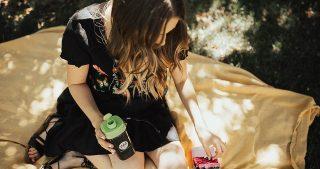girl sitting on blanket with WM nutrition avantraslim in black embroidered dress